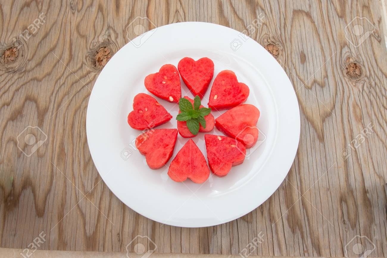 Stock Photo - Watermelon heart shaped and decorate mint on white plate and wooden background. & Watermelon Heart Shaped And Decorate Mint On White Plate And.. Stock ...