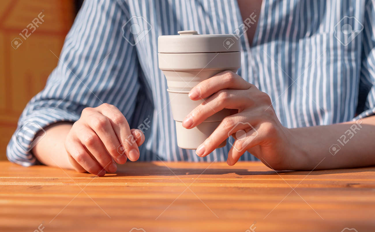 Woman hands closeup holding reusable silicon takeaway eco coffee cup in hands over wooden table. - 172500141