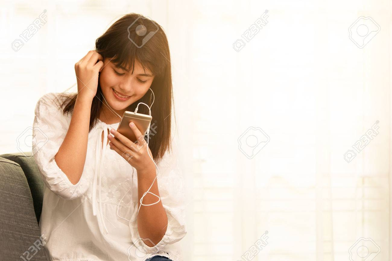 Stock Photo - Young teen Asian girl listening to music with headphone and  smarthphone at home with happiness manner