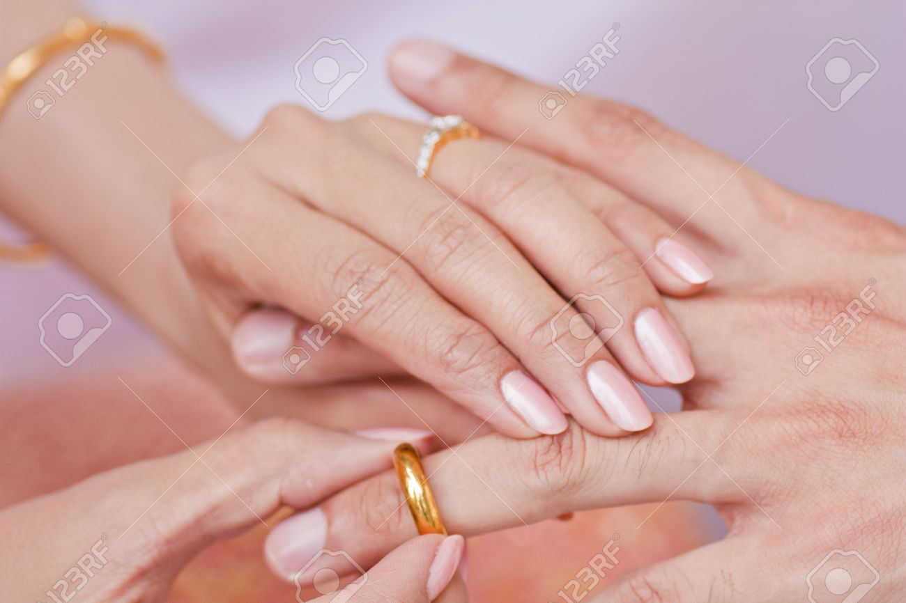 Female Hand Wear Golden Ring In To Male Finger Stock Photo, Picture ...