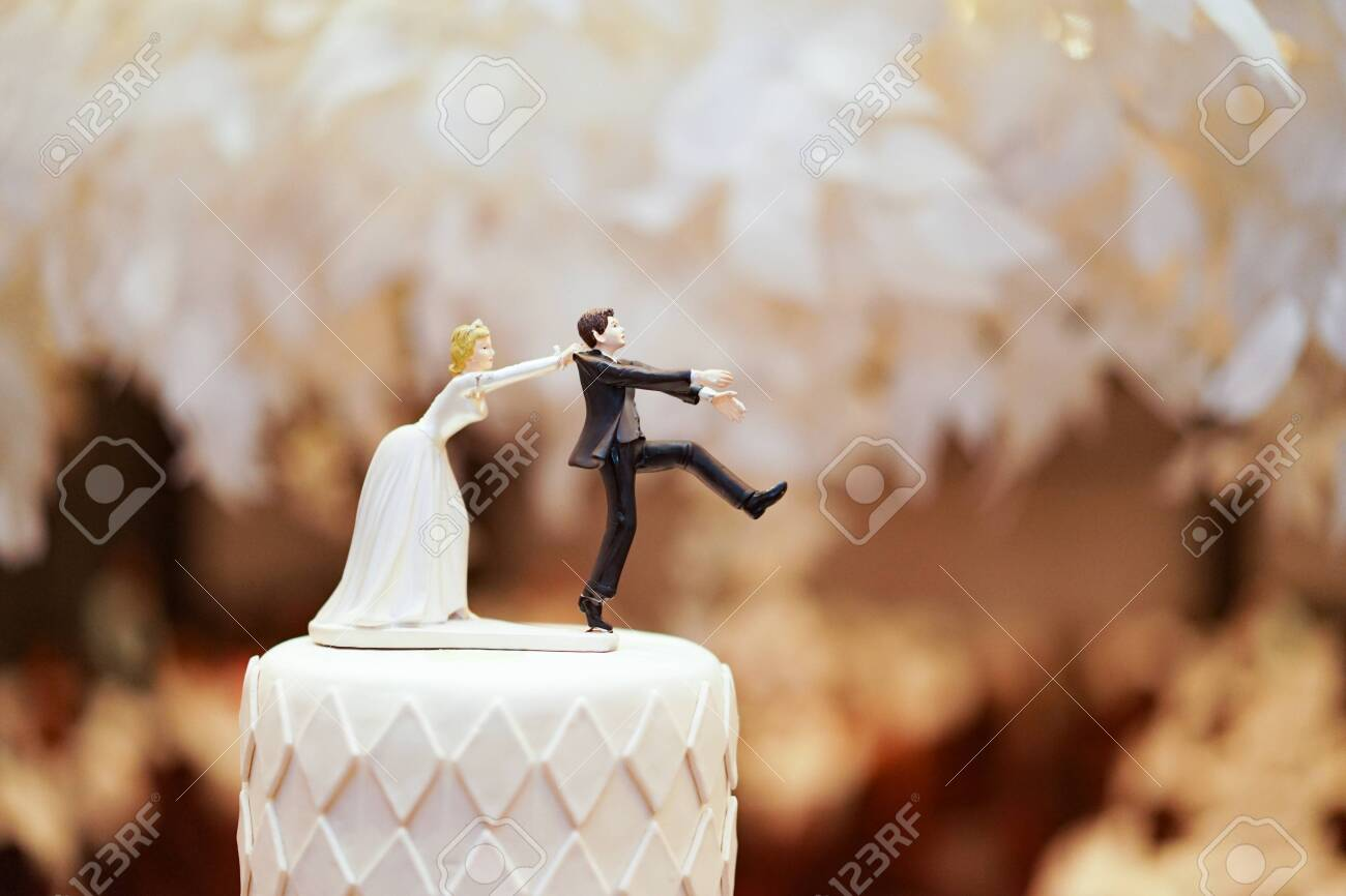 groom doll and statue is running away but bride can catch him finally. the funny wedding story doll on the top of cake. - 128807637