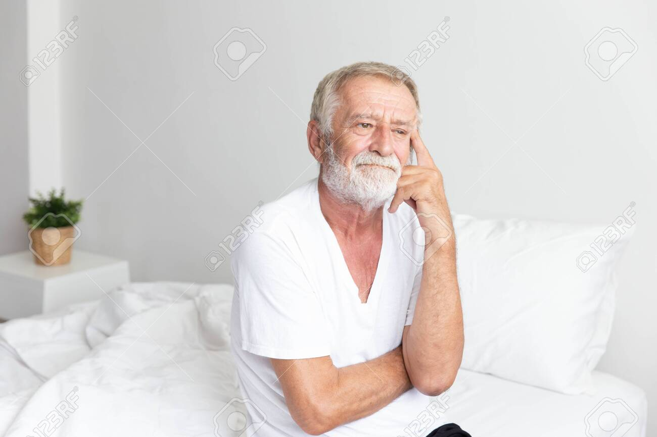 Portrait of a senior retirement man sitting and thinking alone on bed in his home - 149096234