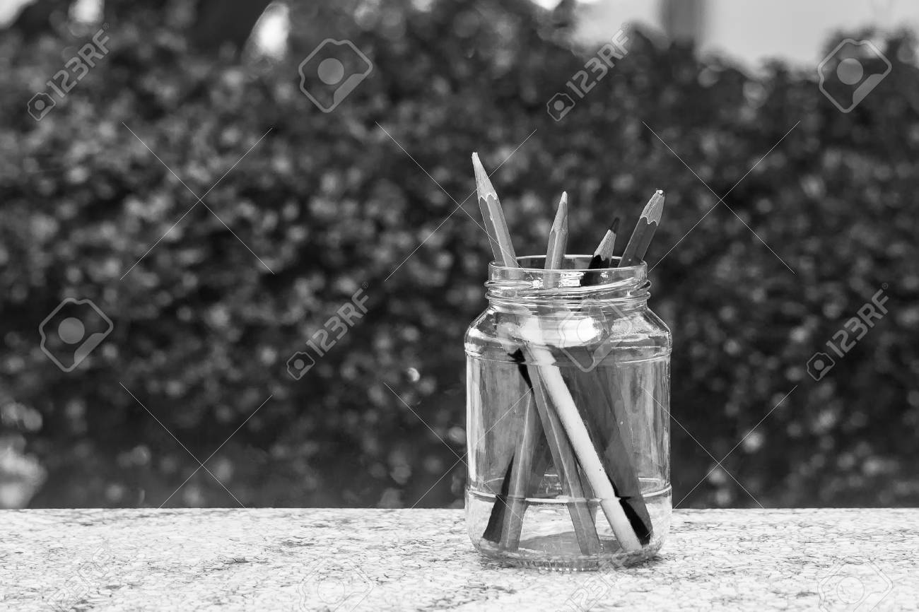Stock photo various pencil in glass bottle on concrete floor with green bush background black and white filter effect