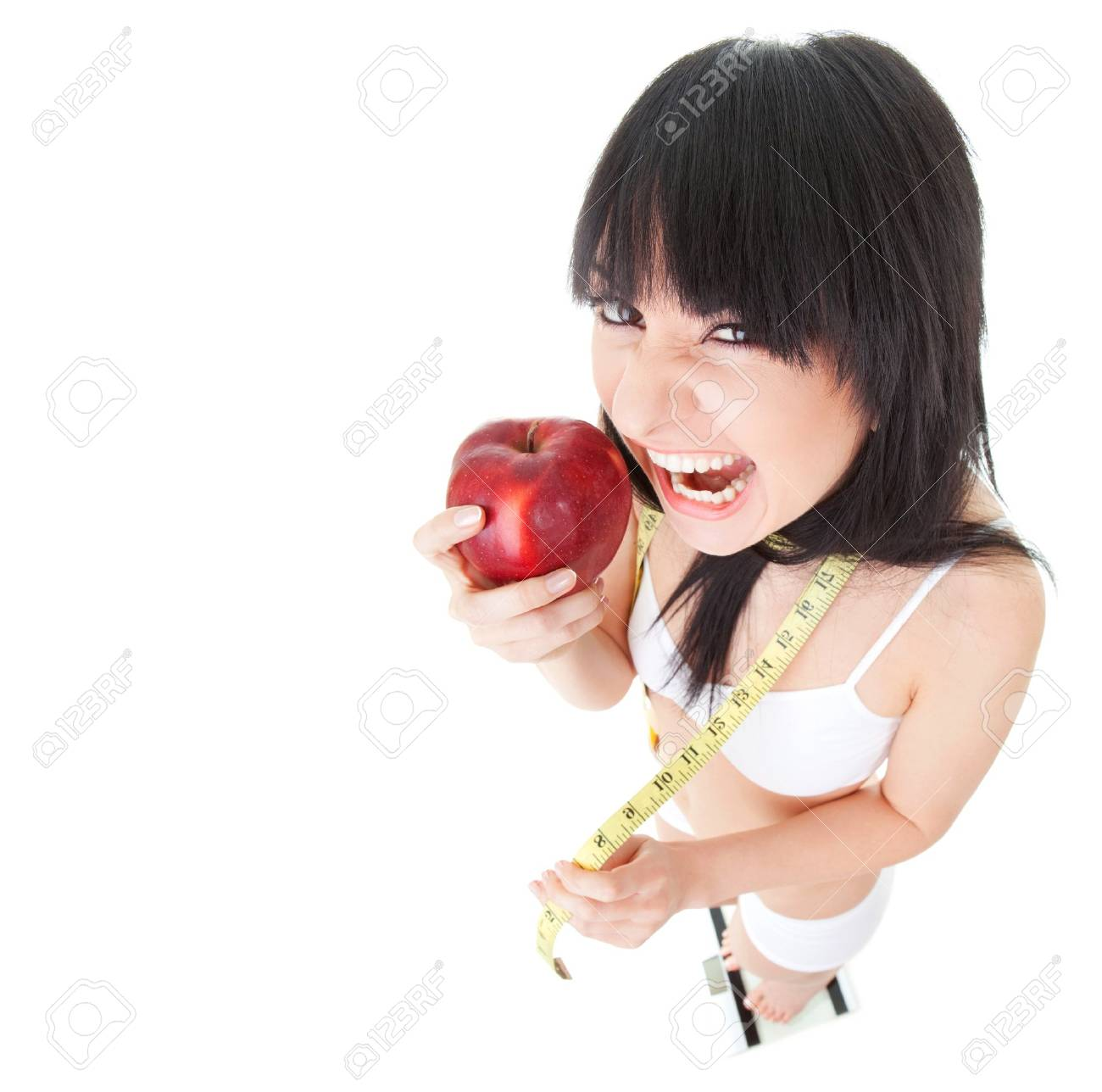 Fun woman with red apple and measure tape on the glass scales Stock Photo - 8311668