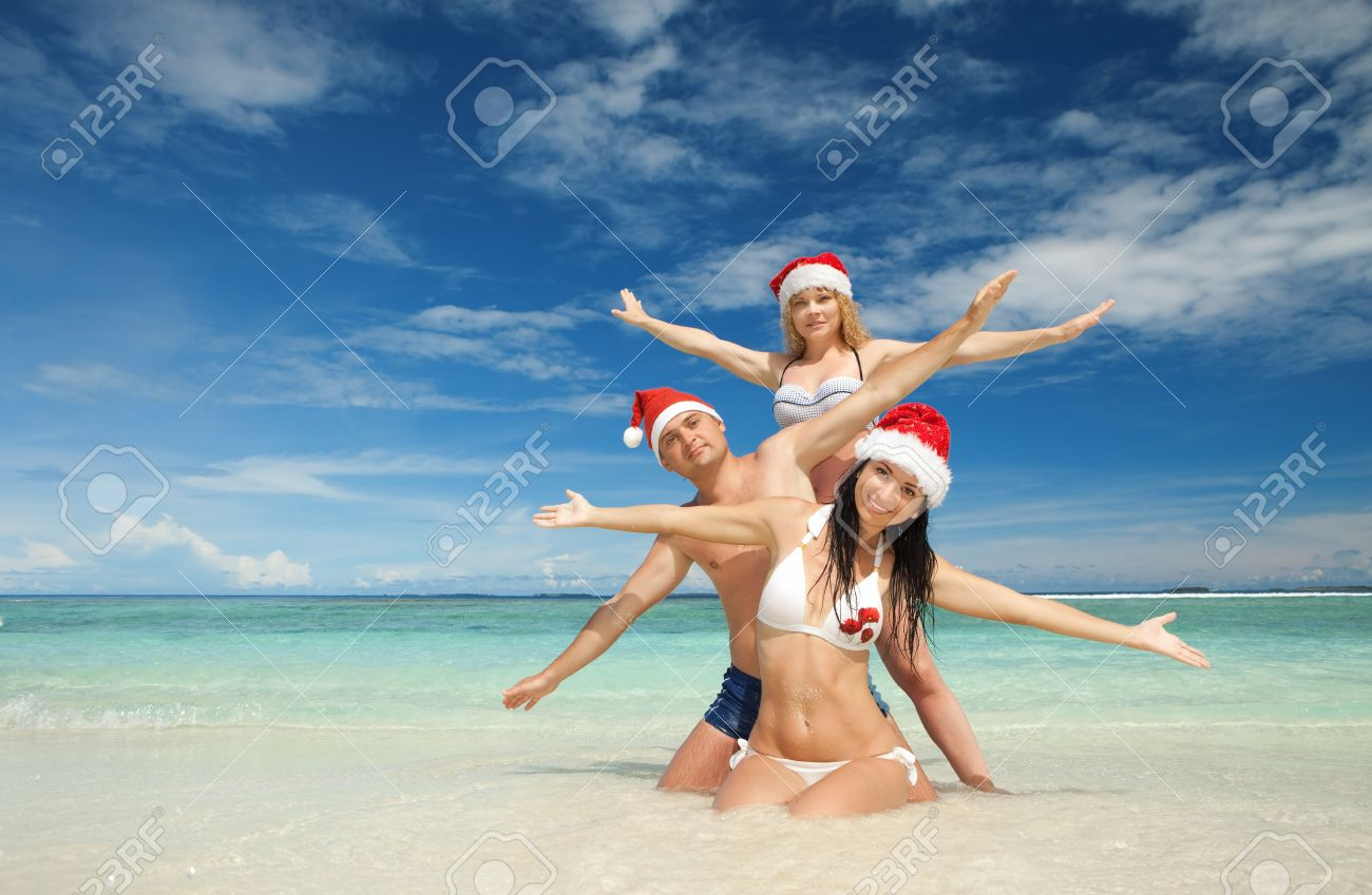 Happy friends in santa hats on the beach. Christmas vacation Stock Photo - 11742476