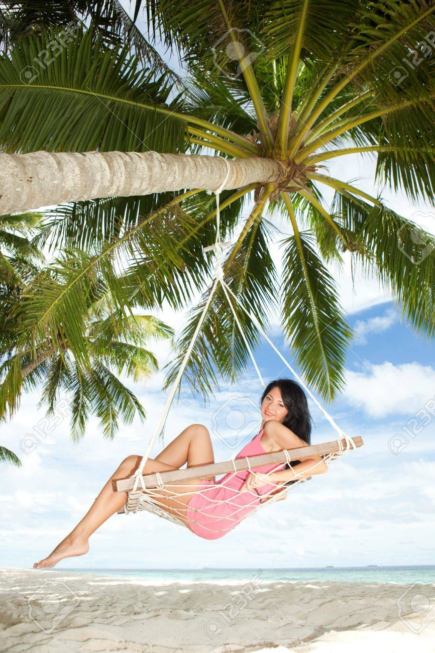 Happy woman relaxing in hammock on a tropical beach Stock Photo - 12941720