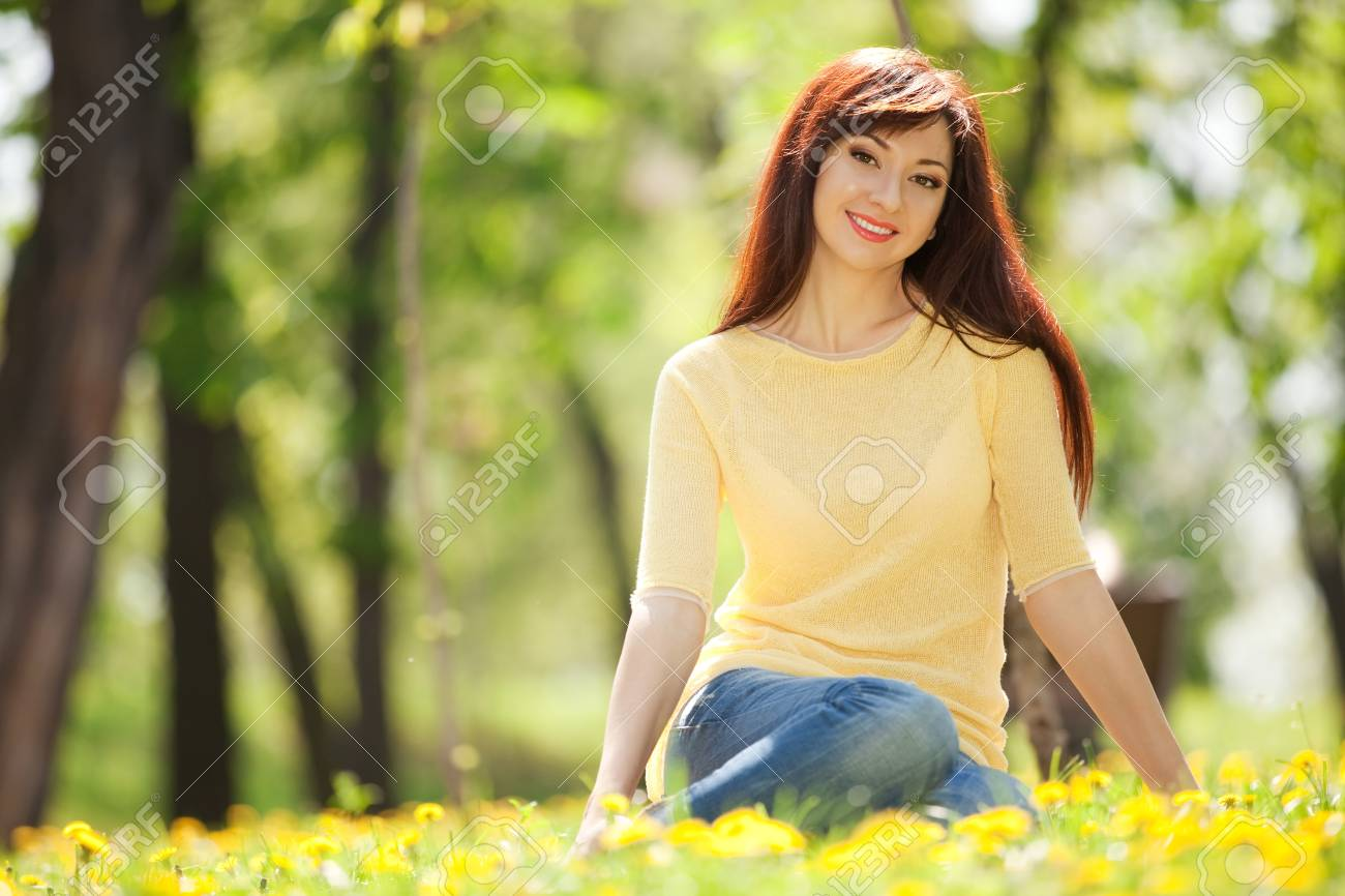 Young redhead woman in the park with flowers Stock Photo - 13765168