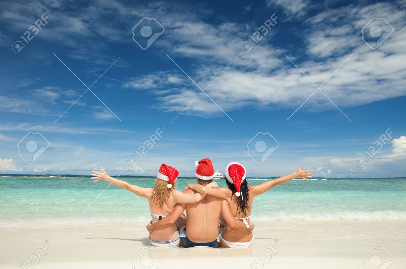 happy friends in santa hats on the beach christmas vacation stock