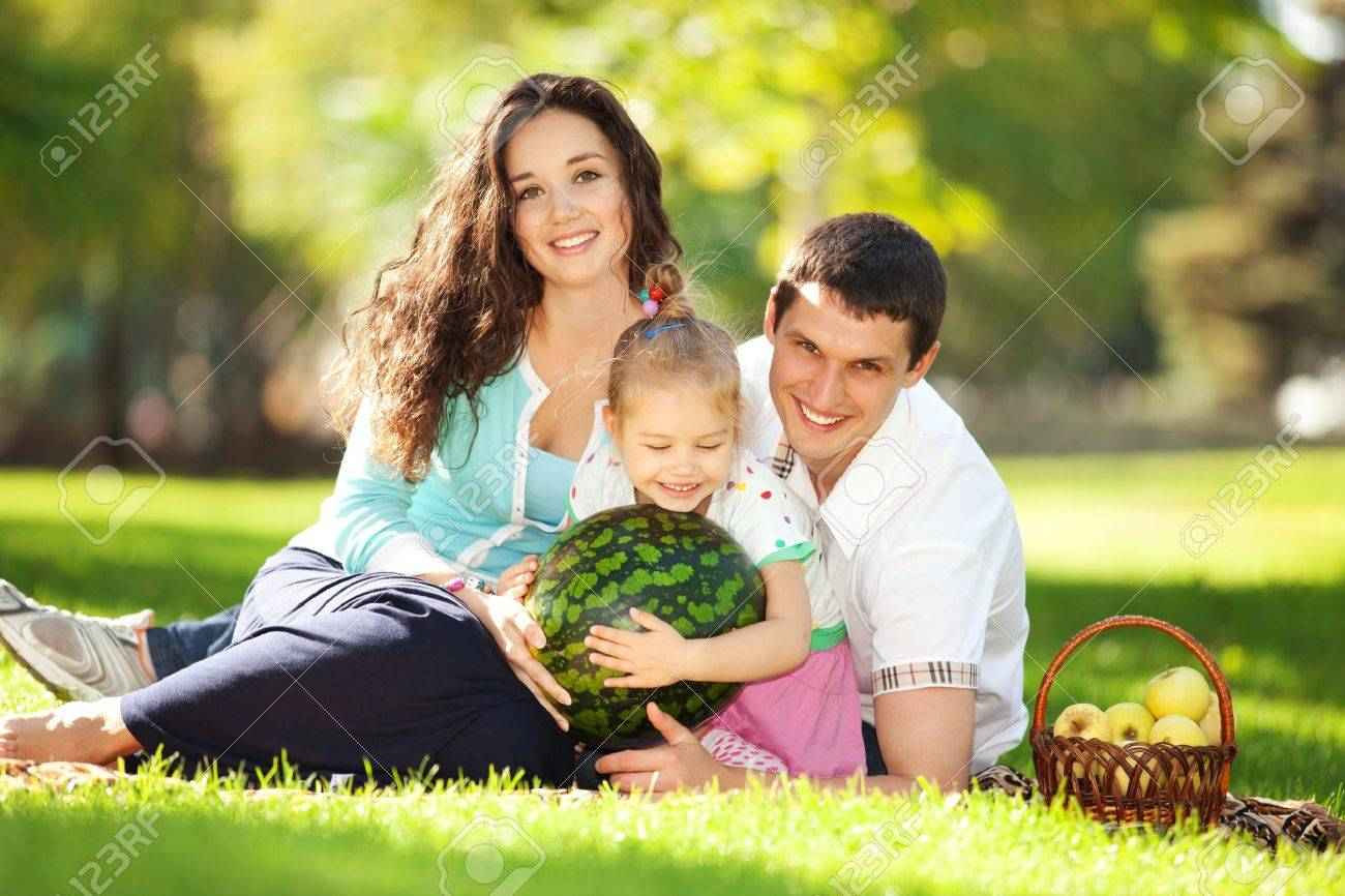 Happy family having a picnic in the green garden - 16694585