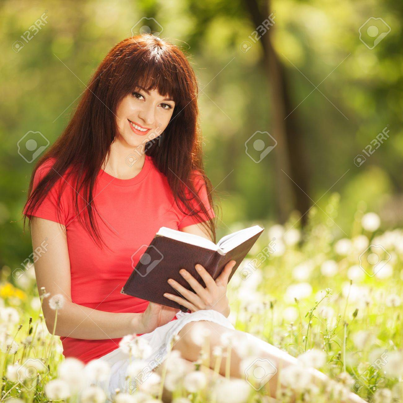 young woman reading a book in the park with flowers stock photo