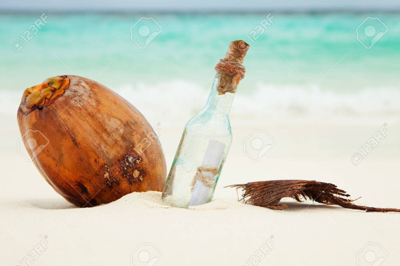 a letter in a bottle and a coconut on the beach stock photo 24556347