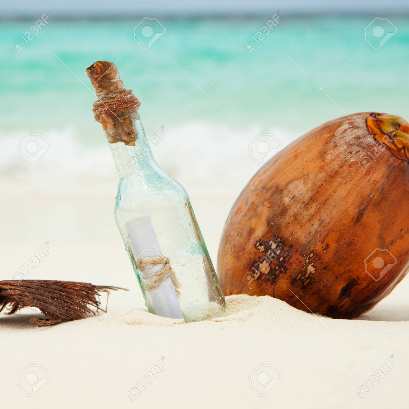 a letter in a bottle and a coconut on the beach stock photo 41190842