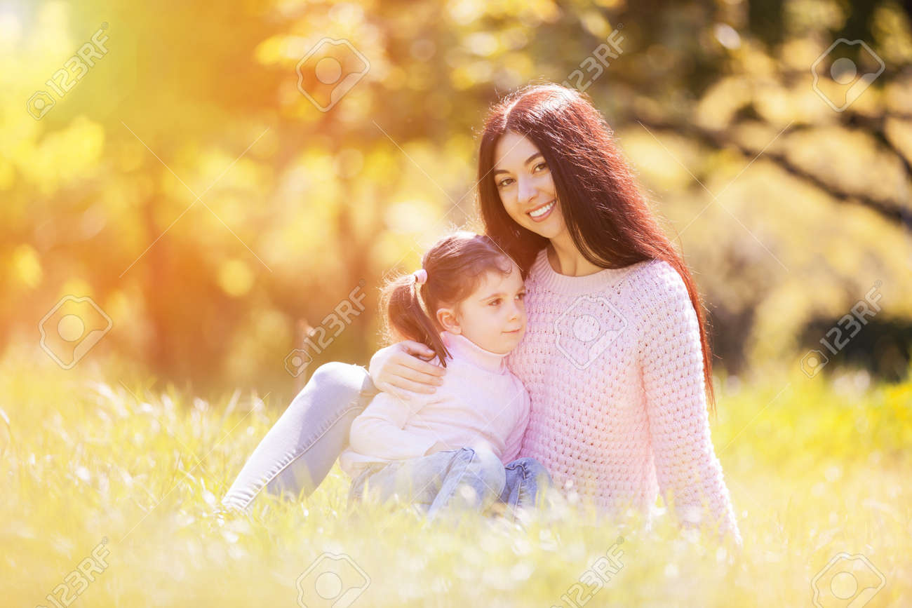 Happy mother and daughter in the autumn park. Beauty nature scene with family outdoor lifestyle. Happy family resting together on grass, having fun outdoor. Happiness and harmony in family life - 157523530