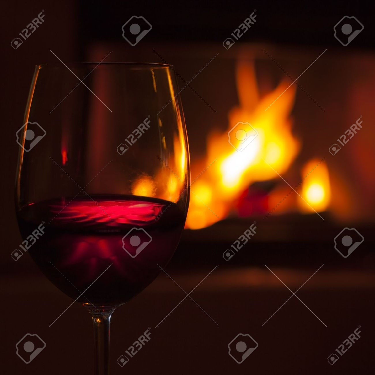 glass of red wine at cozy fireplace in winter stock photo picture