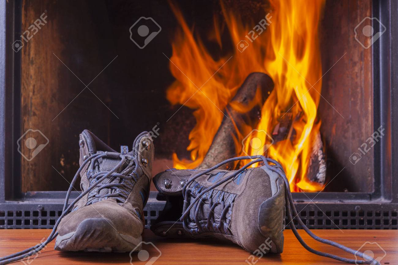 drying hiking shoes at cozy warm fireplace in winter stock photo