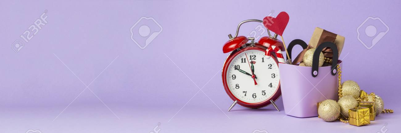 Small plastic bag for shopping, gift boxes, heart on a stick, red alarm clock, Christmas decorations, violet background. Concept of pre-holiday shopping, sale, Black Friday, Cyber Monday. Banner. - 112187385