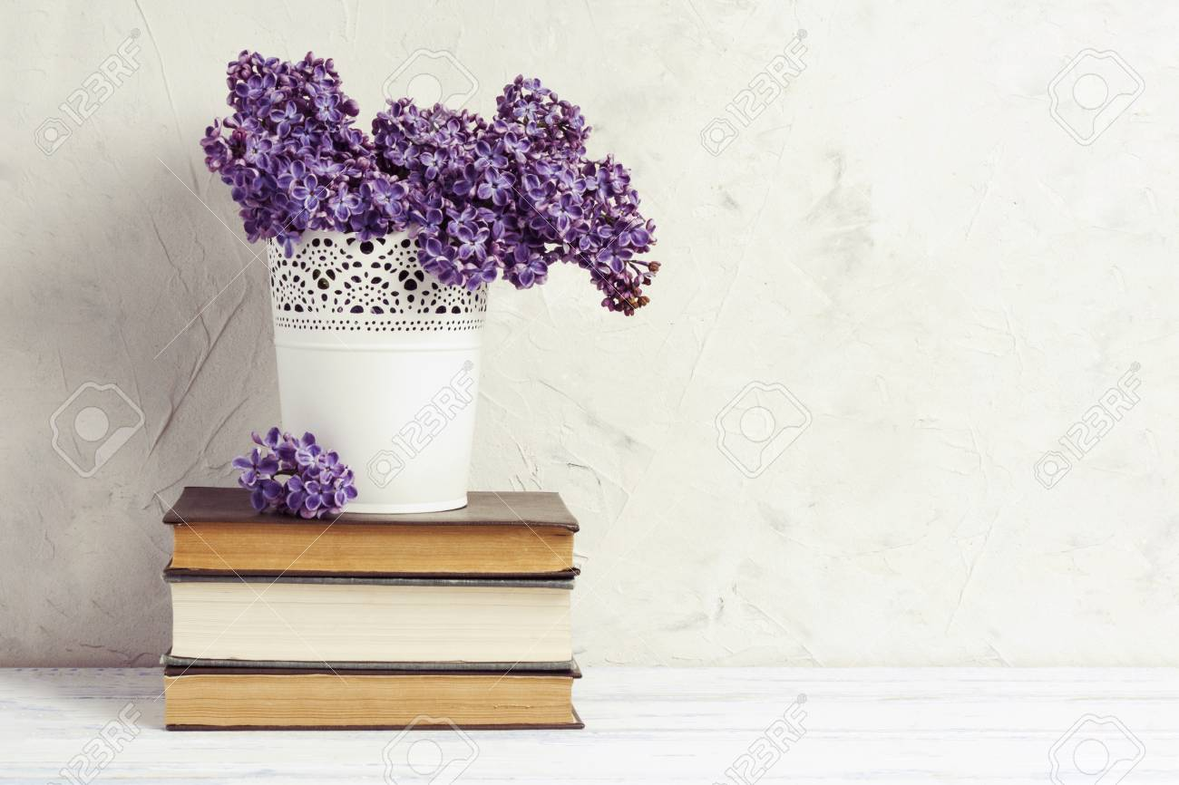 Lilac In A White Decorative Bucket On A Pile Of Books On A White