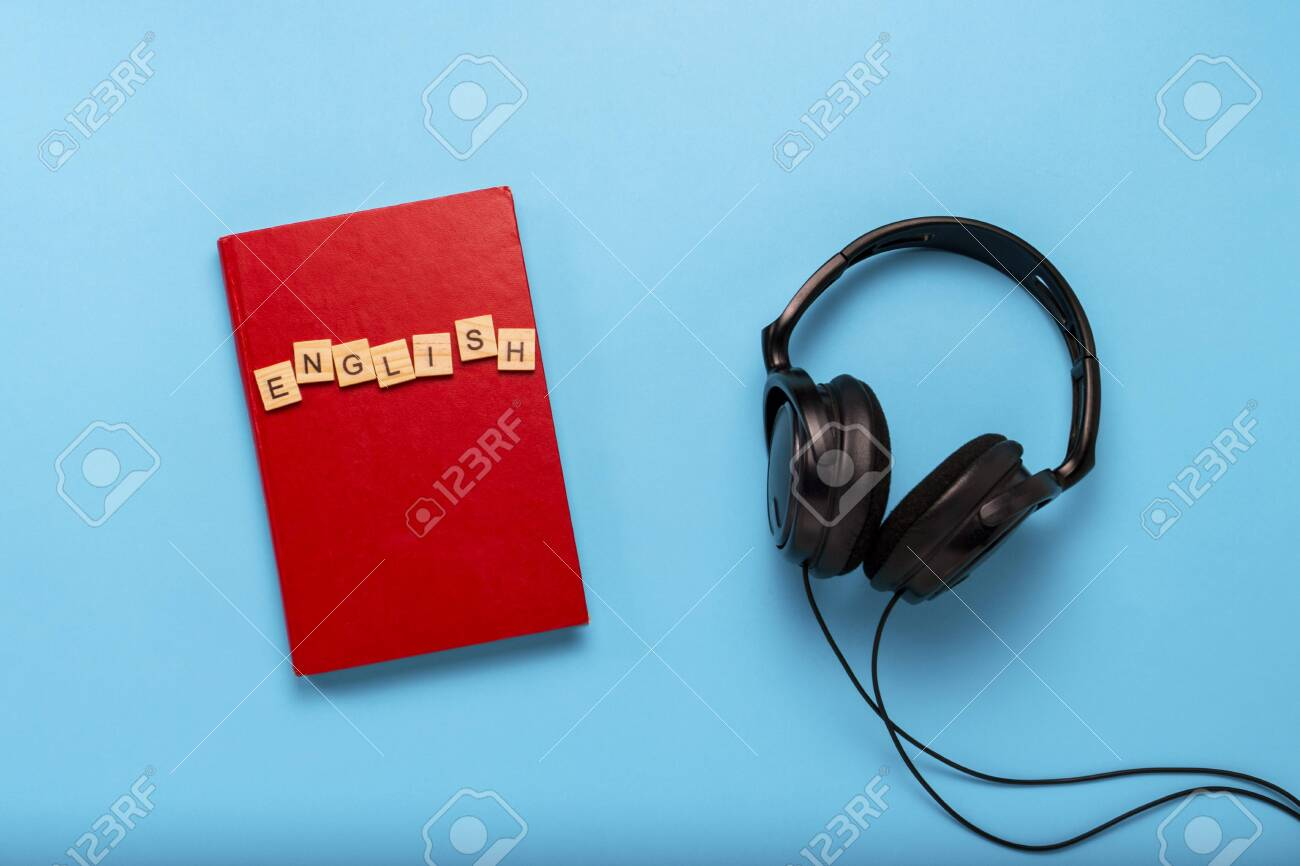 Book with a red cover with text English and black headphones