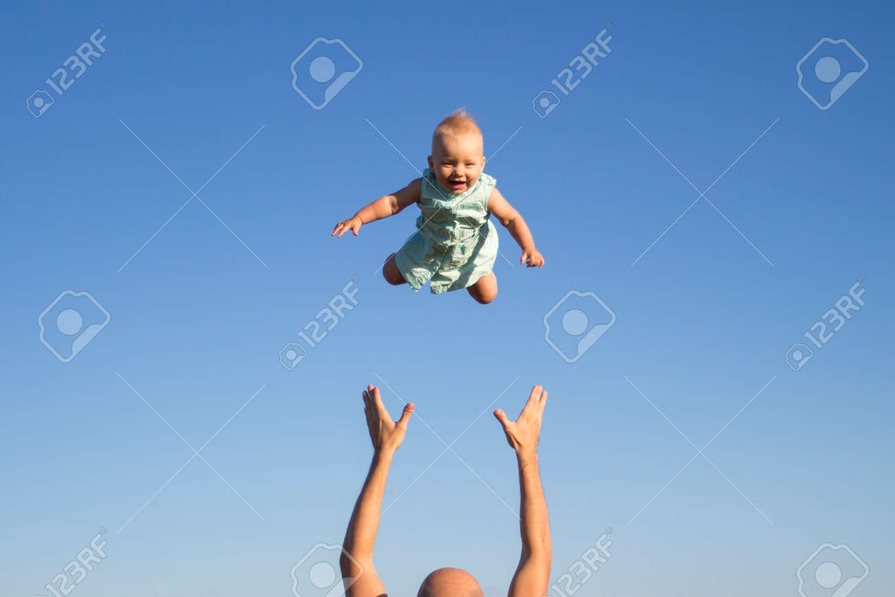 Man throws baby up against the blue sky. Concept game with children, happy family. - 167333843
