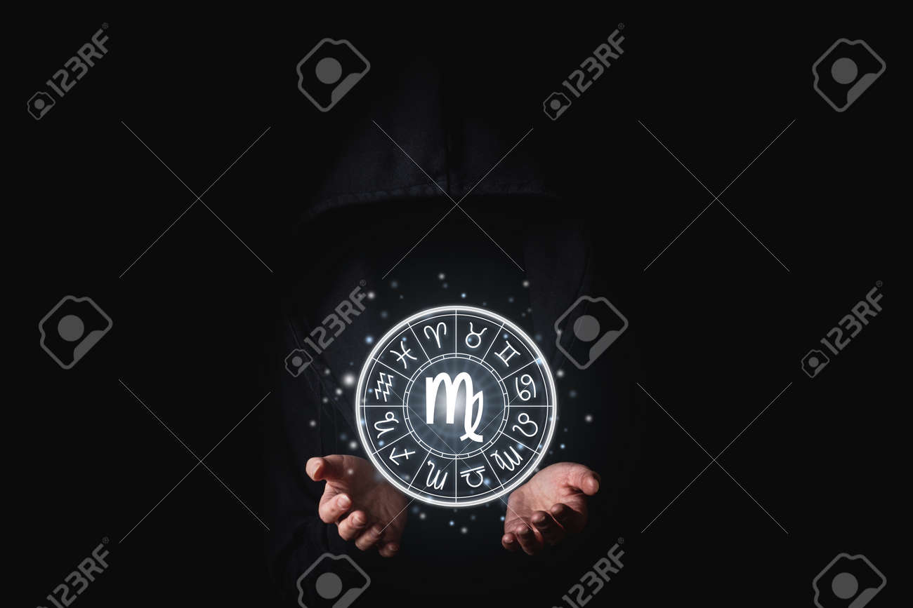 A woman in a black mantle with her palms holds the glowing astrological signs of the zodiacs on a black background. - 171756602