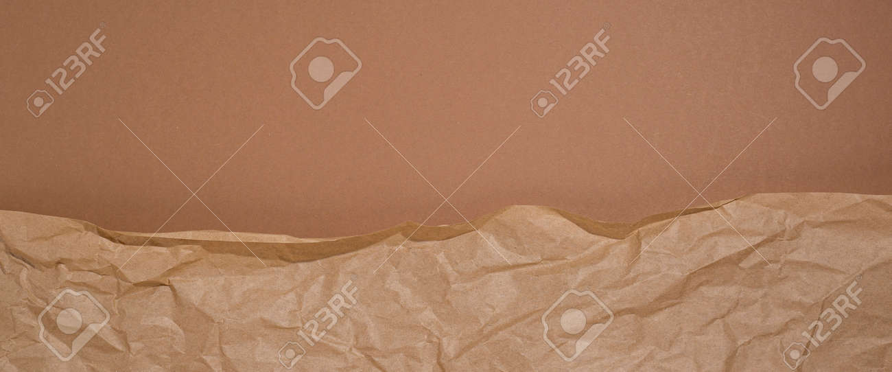 Crumpled craft paper on a brown cardboard background. Banner. - 171756570
