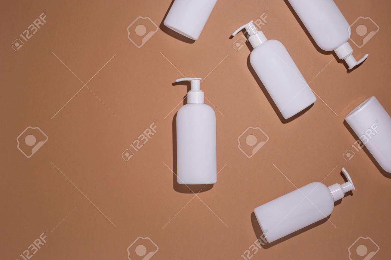 Dispenser bottles lie on a brown cardboard background. Top view, flat lay. - 171847637