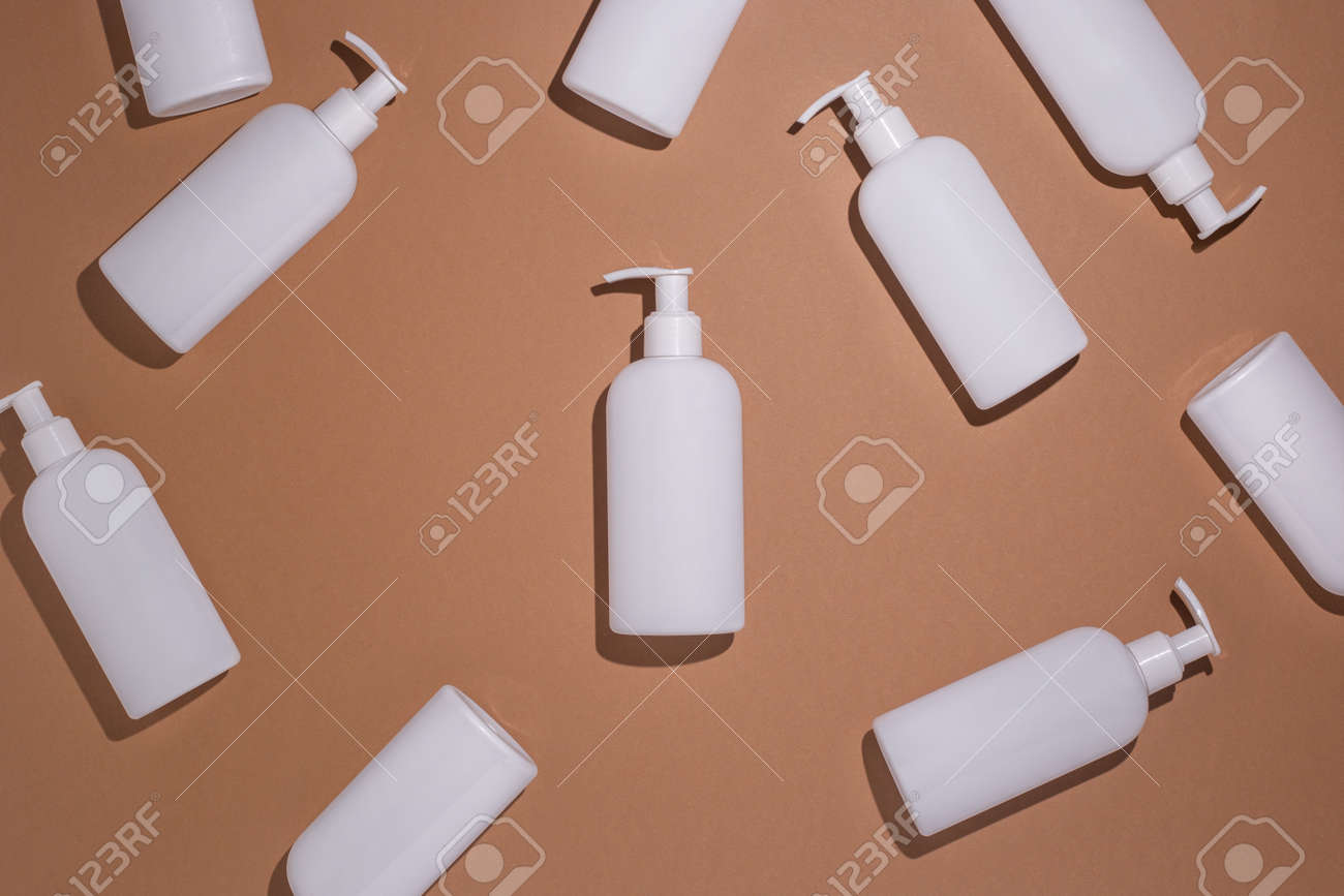 White bottles with a dispenser lie on a brown cardboard background. Top view, flat lay. - 171847639