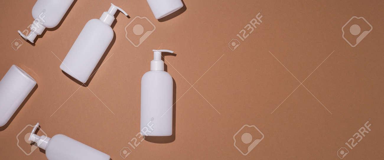 Dispenser bottles lie on a brown cardboard background. Top view, flat lay. Banner. - 171847642