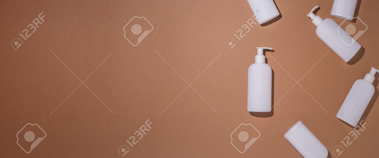 Dispenser bottles lie on a brown cardboard background. Top view, flat lay. Banner. - 171847651