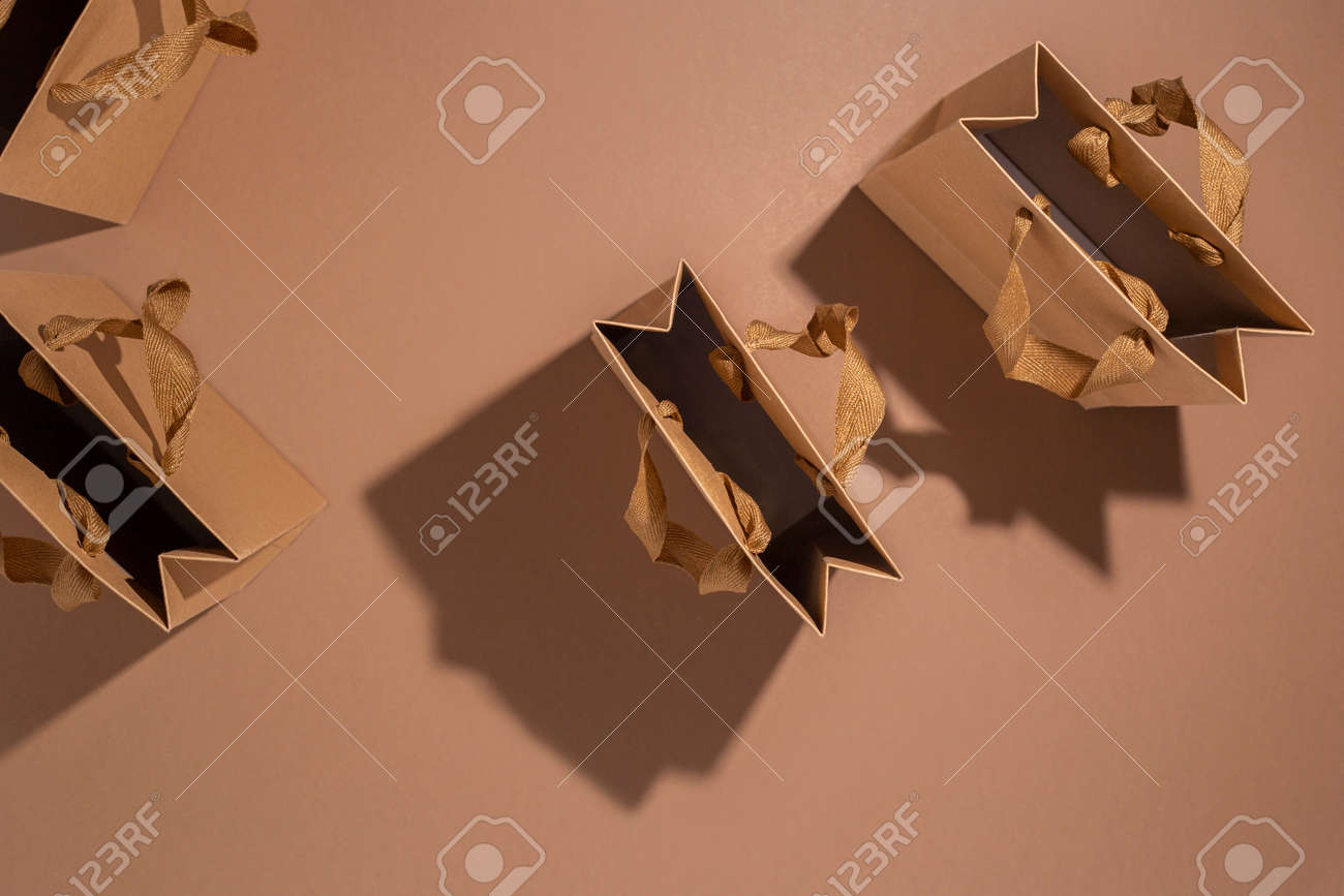 A lot of craft gift bags on a brown background. Top view, flat lay. - 171847655
