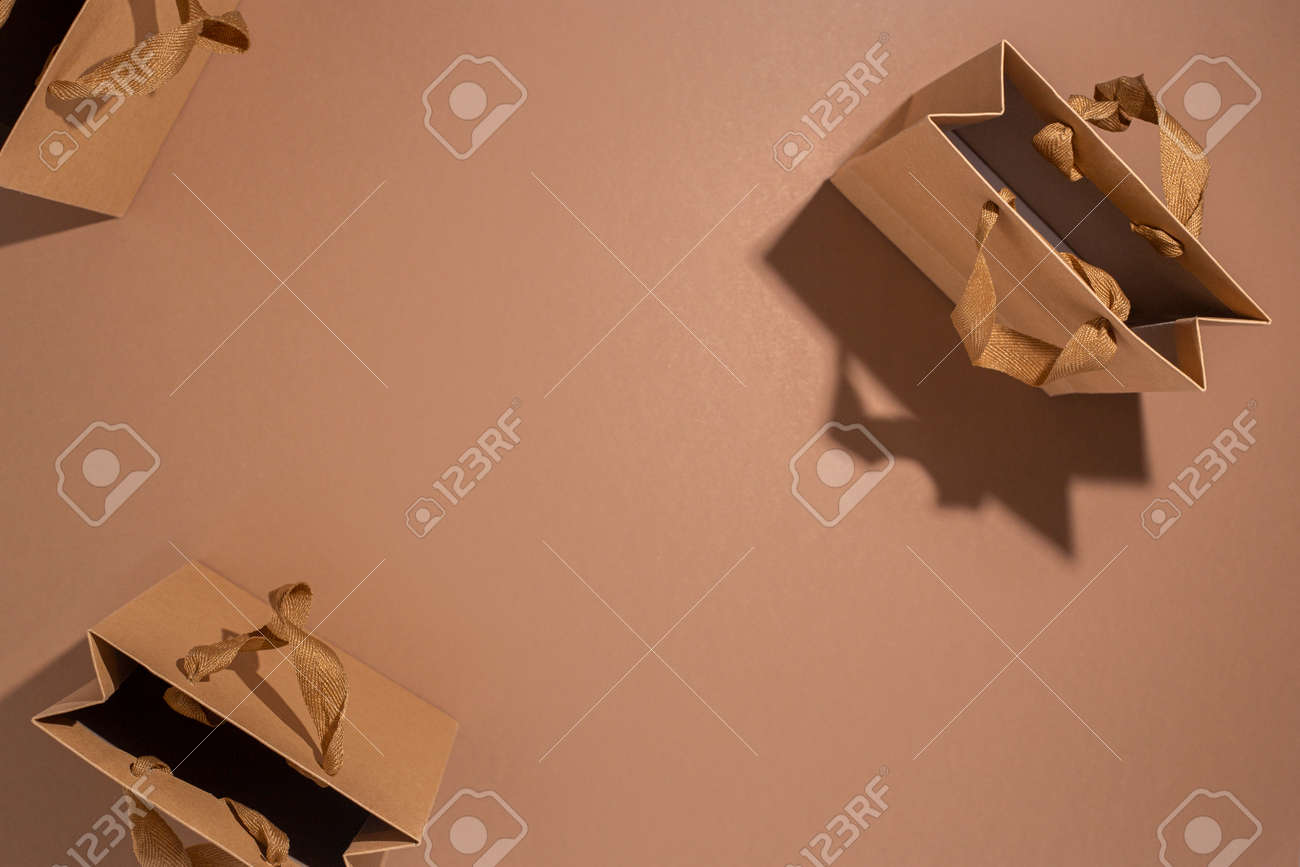 Three craft gift bags with satin ribbon on brown background. Top view, flat lay. - 171847662