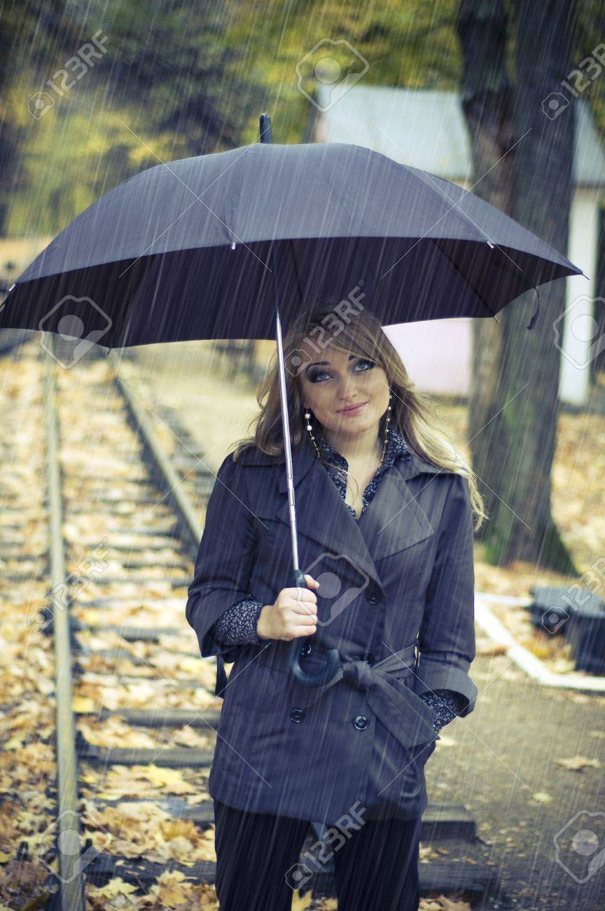 beautiful woman with blonde long hair at autumn park. it's raining Stock Photo - 4592530