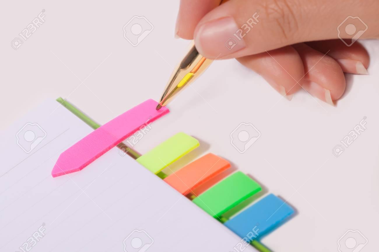Female hand writing bookmark on notebook Stock Photo - 10849443
