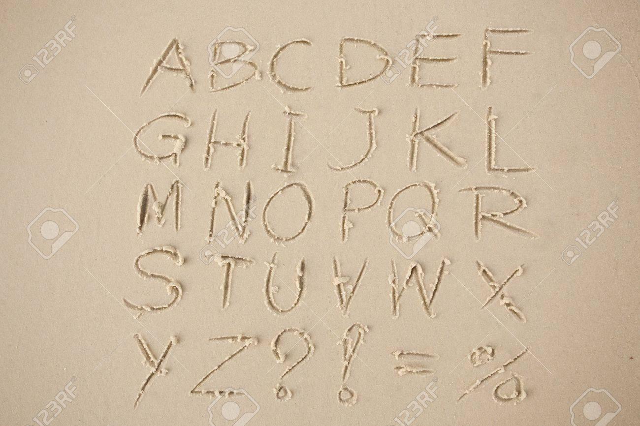 stock photo the alphabet written in sand on a beach