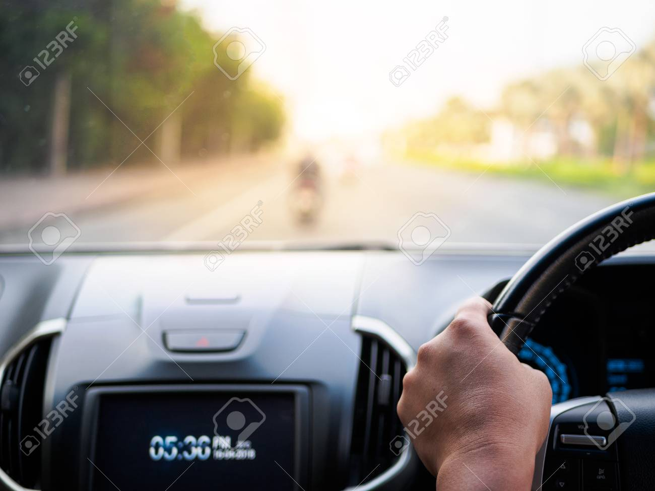 Man's hands holding steering wheel and blur road background. Driving concept - 100024816