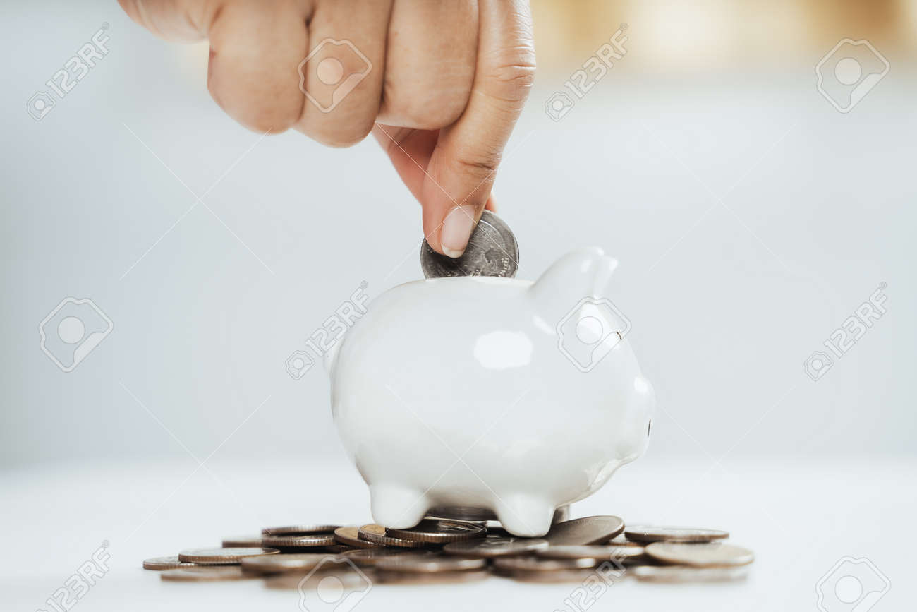 Close up of woman hand putting money coin into piggy bank for saving money. saving money and financial concept - 171421875