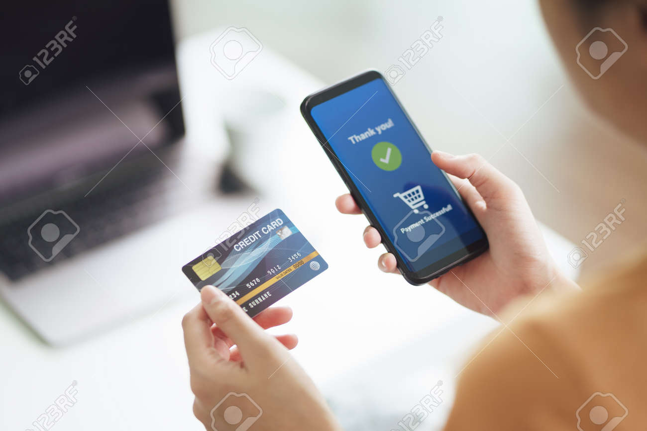 Young woman holding credit card and using smart phone for online shopping, internet banking, e-commerce, spending money, working from home concept - 171558480