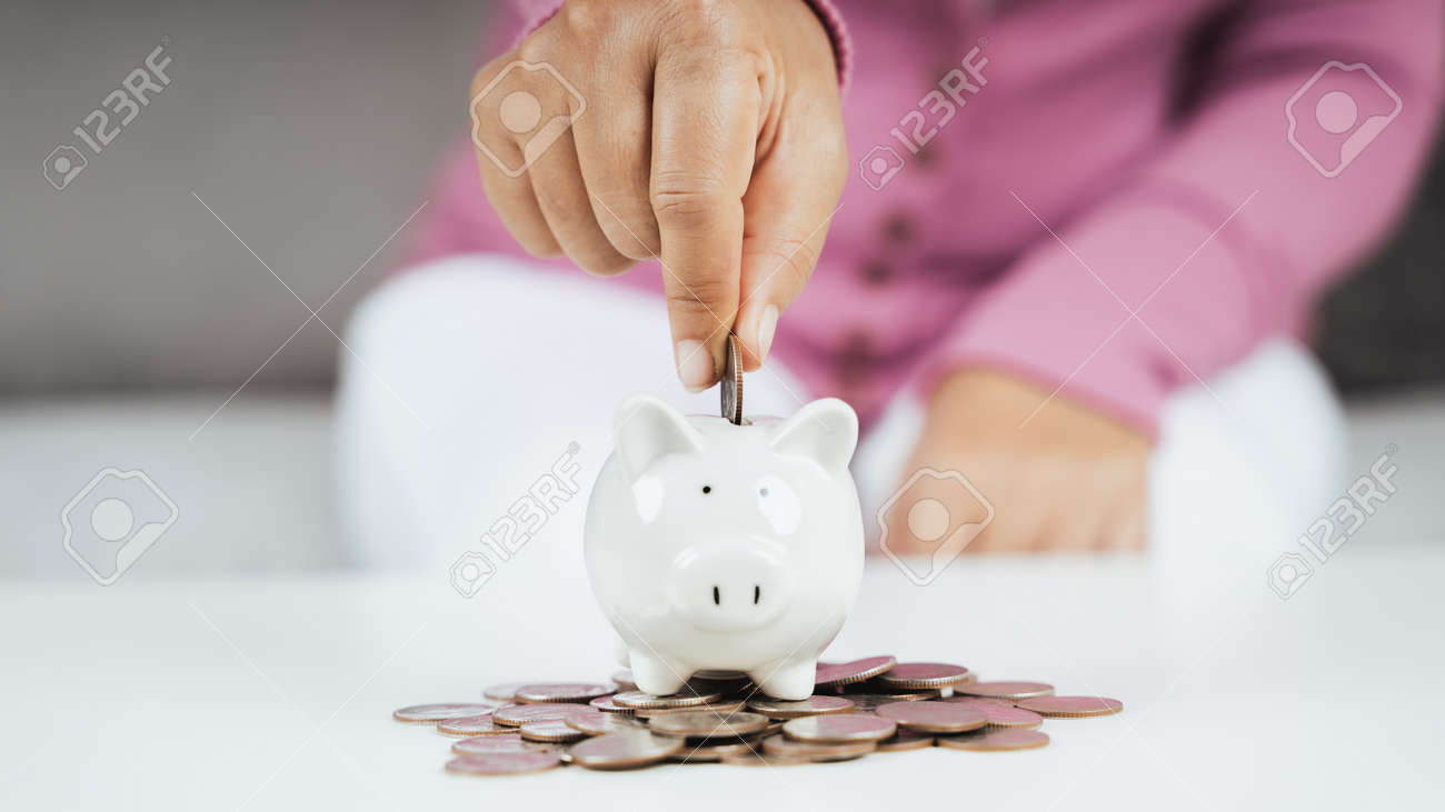 Close up of woman hand putting money coin into piggy bank for saving money. saving money and financial concept - 171723907