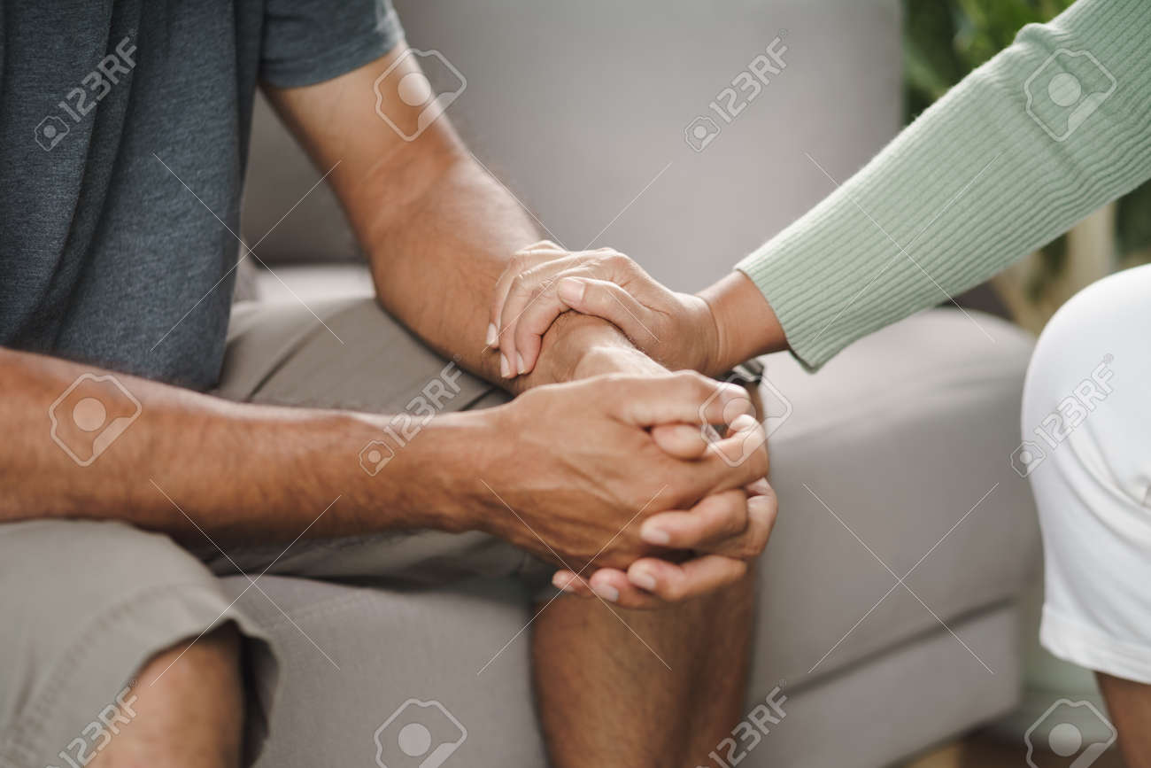 Female friend or family sitting and hold hands during cheer up to mental depress man, Psychologist provides mental aid to patient. PTSD Mental health concept - 171880905
