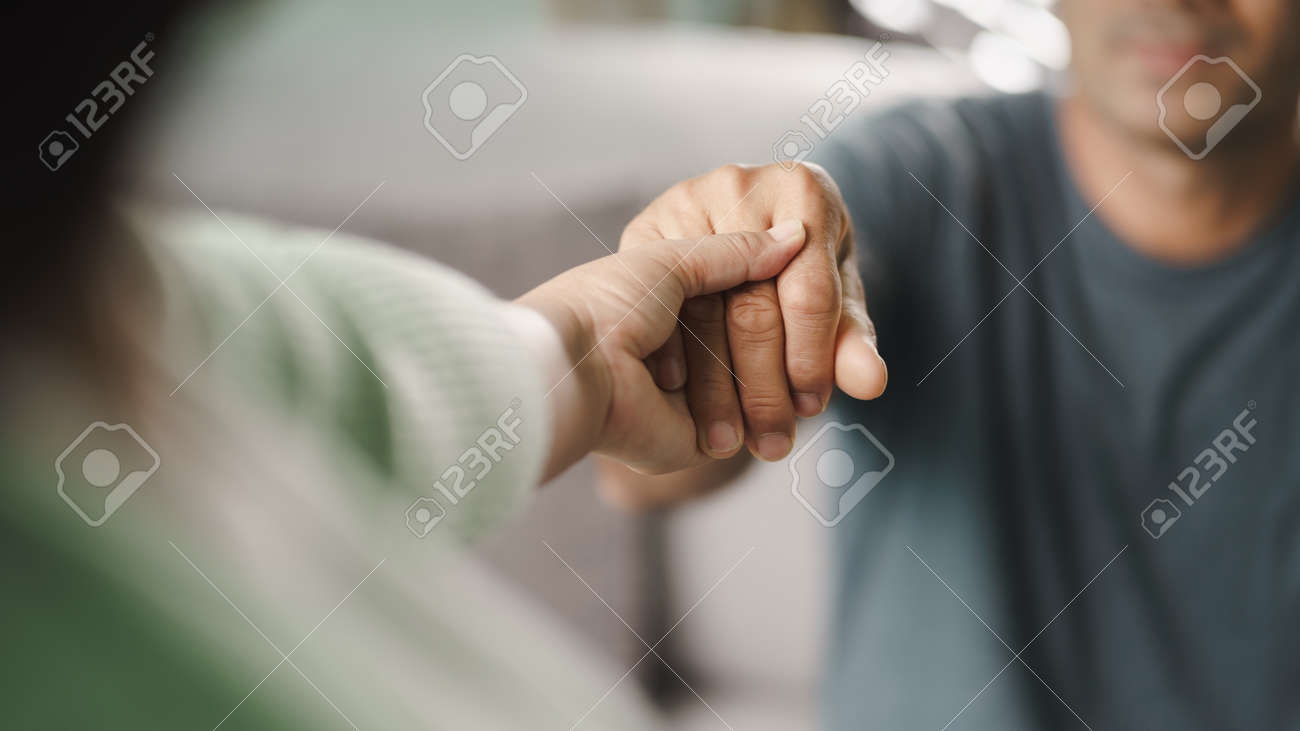 Female friend or family holding hands during cheer up to mental depress man, Psychologist provides mental aid to patient. PTSD Mental health concept. - 171880907