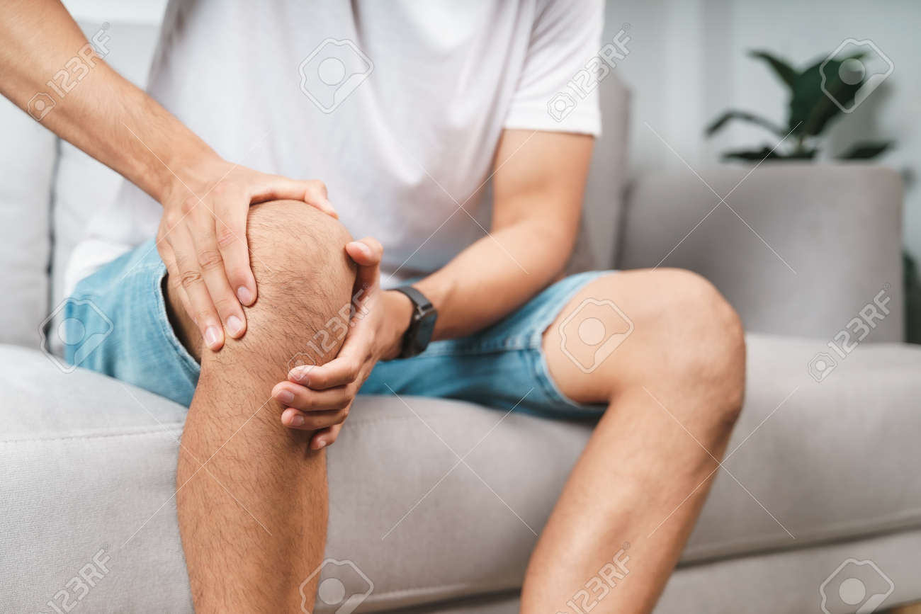 The man suffering from knee pain sitting on the couch hold and massaging his painful knee. - 171855962