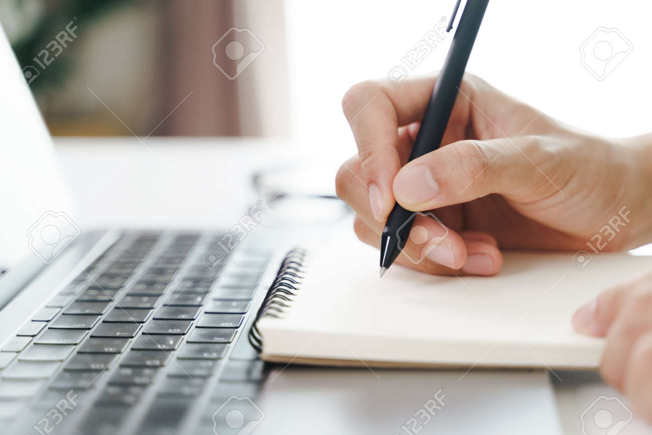 Close up of young man in casual cloth hands writing down on the notepad, notebook using ballpoint pen with laptop computer on the table. - 171856036