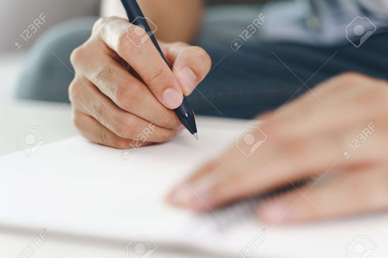 Close up of young man in casual cloth hands writing down on the notepad, notebook using ballpoint pen on the table. - 171856176