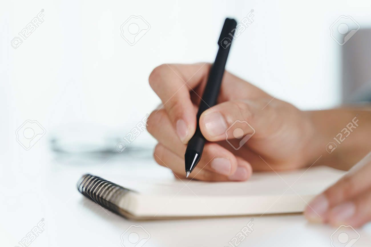 Close up of young man in casual cloth hands writing down on the notepad, notebook using ballpoint pen on the table. - 171855903