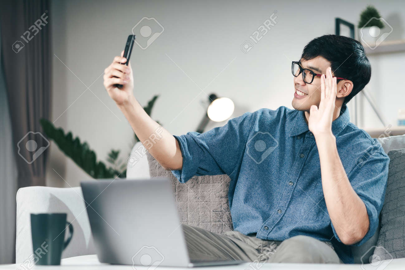 Young Asian man using smartphone for online video conference call and waving hand making hello gesture in the living room. - 171949171