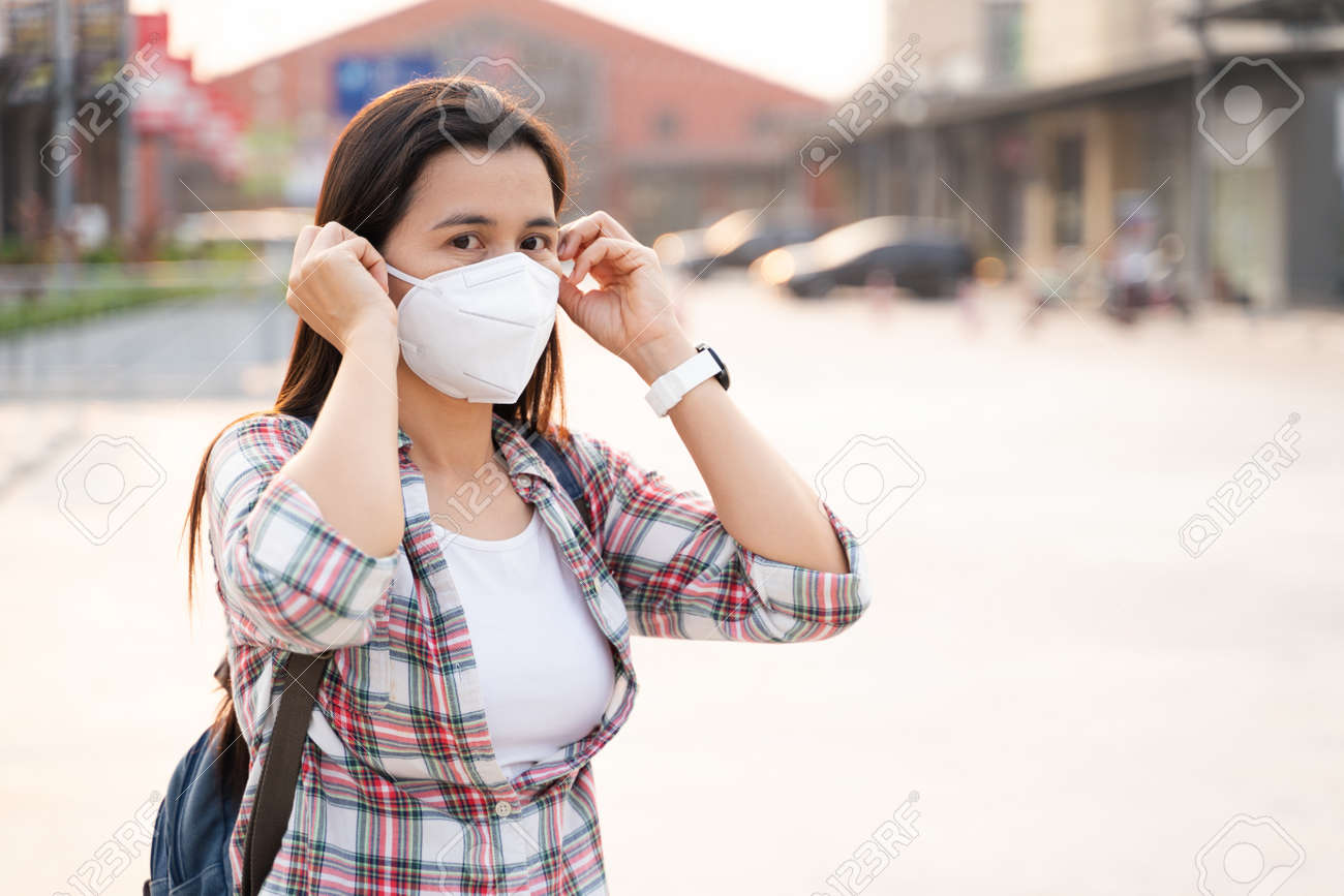 Asian woman wearing N95 face mask to protect pollution PM2.5 and virus. COVID-19 Coronavirus and Air pollution pm2.5 Healthcare and medical concept. - 171949183