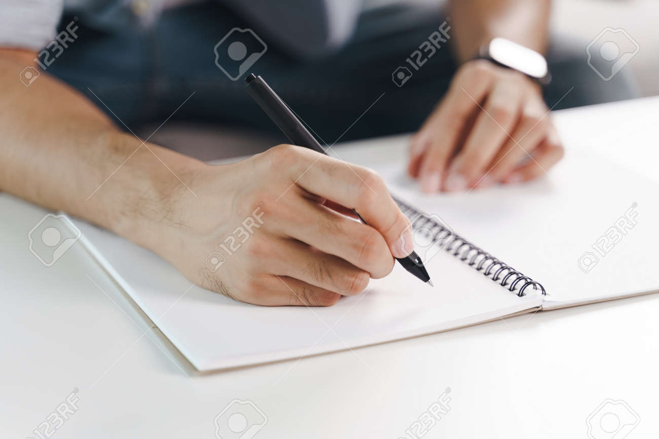 Close up of young man in casual cloth hands writing down on the notepad, notebook using ballpoint pen on the table. - 171935709