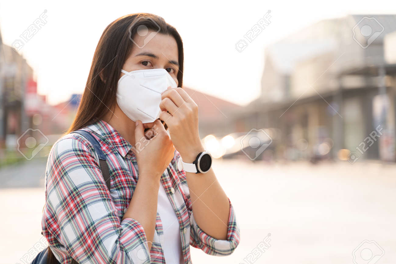 Asian woman wearing N95 face mask to protect pollution PM2.5 and virus. COVID-19 Coronavirus and Air pollution pm2.5 Healthcare and medical concept. - 171949185