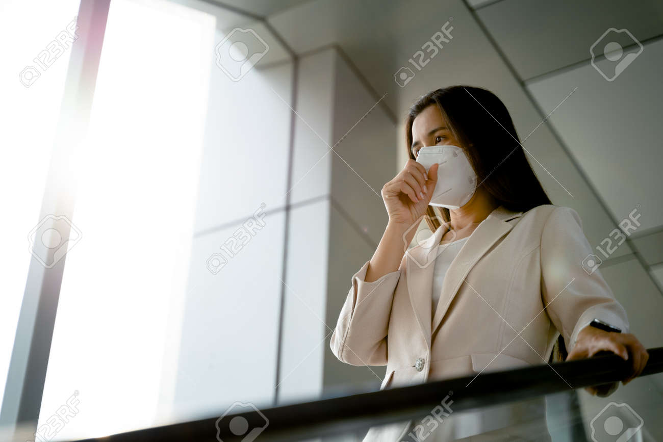 Asian woman wearing N95 face mask to protect pollution PM2.5 and virus. COVID-19 Coronavirus and Air pollution pm2.5 Healthcare and medical concept. - 171949186