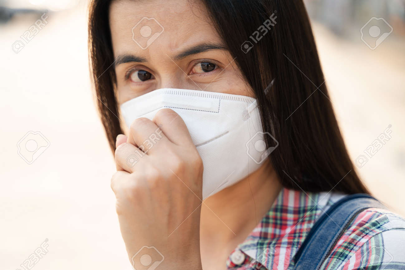 Asian woman wearing N95 face mask to protect pollution PM2.5 and virus. COVID-19 Coronavirus and Air pollution pm2.5 Healthcare and medical concept. - 171949138